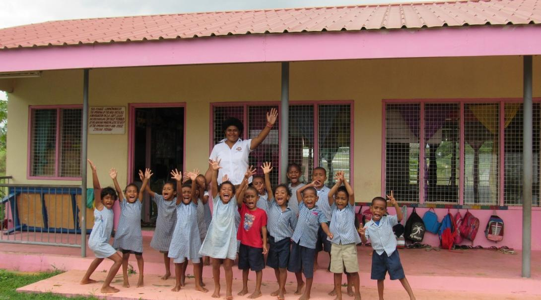 A group of children pose for a photo with their teacher outside a kindergarten at one of our Childcare volunteer placements in Fiji.